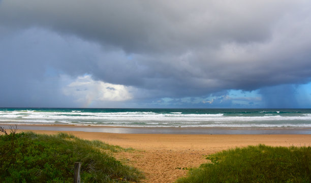 Dramatic sky with large clouds over Arrawarra beach (North Coast, NSW,  Australia). Gushing sea on a cloudy day. Horizontal view of dramatic overcast sky and sea. Fifty shades of blue and grey.