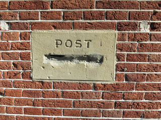 post mortem, a post box or mailbox stopped up with cement in a red brick wall