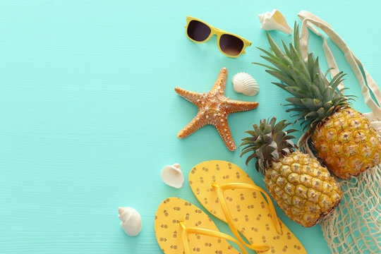 Ripe pineapple and beach sea life style objects over pastel mint blue wooden background. Tropical summer vacation concept