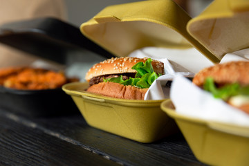 Aluminium Prints Food Hamburger in a takeaway container on the wooden background. Food delivery and fast food concept