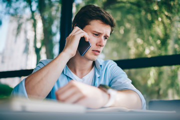 Frustrated young man 20 years old unhappy with bad news head during phone call on smartphone device.Upset hipster guy dressed in casual wear talking on cellular about solving problem