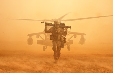 Poster Helicopter Military soldier walking at desert with gun on his shoulder in front of helicopter in sand storm.