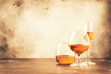 Poster Alcohol Selection of hard strong alcoholic drinks and spirits in assortment: cognac, brandy and rum. Gray bar counter background, selective focus, copy space