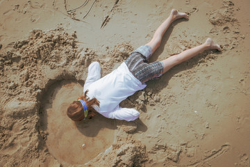 Girl playing in sand at the beach