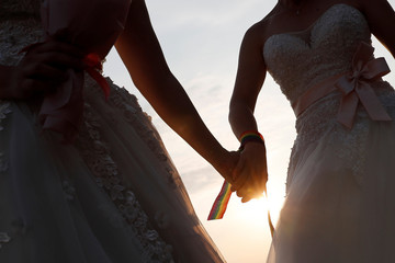 A newlywed lesbian couple in wedding dresses holds hands at a mass wedding banquet, one day after same-sex marriage officially became legal, in Taipei