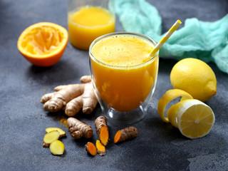 Foto auf Acrylglas Saft Turmeric or curcuma drink with ginger, healthy detox vitamin orange juice
