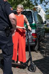 Frau mit Elektroroller spricht mit Polizei