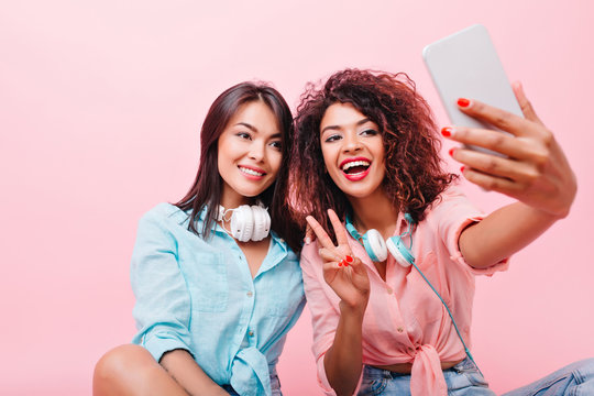 Pleased tanned asian girl gently smiling while her african friend making selfie. Indoor portrait of glad black woman with smartphone taking picture of herself on pink background near hispanic lady.