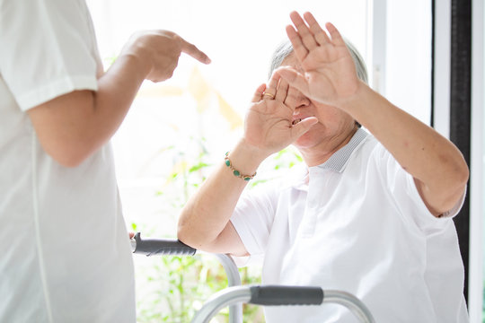 Asian elderly woman were physically abused,attacking in house,angry man raised punishment fist,stop physical abuse senior people,caregiver,family stop violence and aggression concept.
