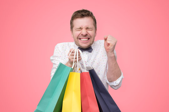 man holding pile of bags with gifts with shock