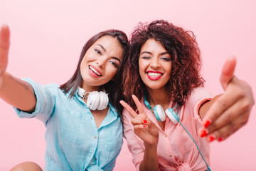 Joyful asian lady with bronze skin making selfie with african curly girl. Blissful mulatto woman in headphones smiling while taking picture of herself during fun with friend.