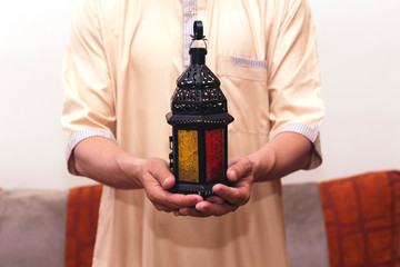 Arab Muslim man holding lantern ready for eid  and Ramadan Kareem concept.
