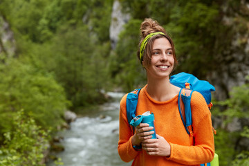 Positive female tourist wanders near mountain river in wood, poses against nature composition, focused aside gladfully, drinks hot beverage, dressed in orange jumper. People and adventure concept