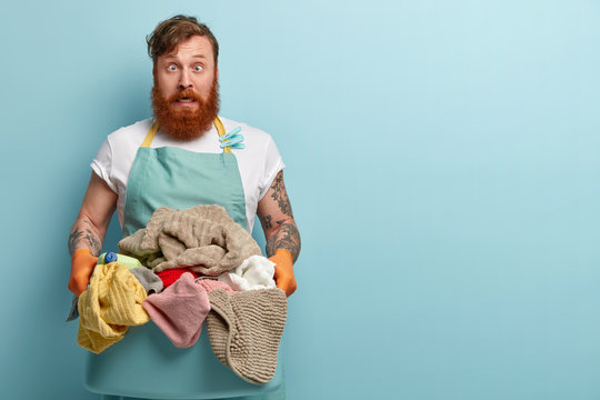 Crazy redhead man foolishes indoor, crosses eyes, wears casual apron and rubber gloves, foolishes indoor, carries pile of laundry to washing machine, stands over blue background with empty space
