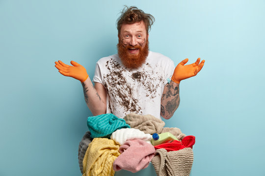 Happy red haired man with thick bristle, spreads hands, has fun after doing laundry at home, dressed in white dirty t shirt, poses over blue background. People, emotions and domestic work concept