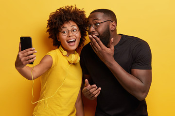 Joyous dark skinned female and male couple have fun together, pose for making selfie portrait, smile broadly at camera, use stereo headphones for listening music, isolated over yellow background