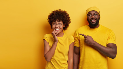 Studio shot of happy young woman and man look happily aside, point at blank space, notices awesome product, stand against yellow studio background. People, advertisement and ethnicity concept