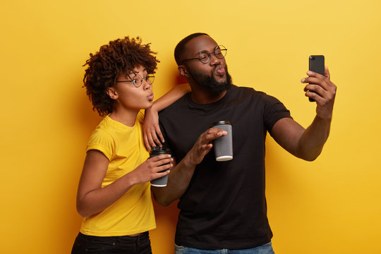 Funny dark skinned couple pouts lips at camera of cell phone, make selfie portrait, drink coffee to go from disposable cups, wear black and yellow t shirts, round spectacles, pose indoor, have fun