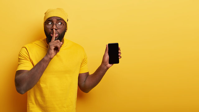 Embarrassed black man makes shush gesture, tries be speechless, looks secretly aside, holds modern cell phone device with mock up screen, tells secret functions of cellular, isolated on yellow wall