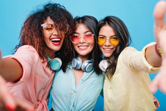 Joyful hispanic girl in yellow cotton shirt making selfie with her international female friends. Charming curly african woman taking picture of herself during party with latin ladies.