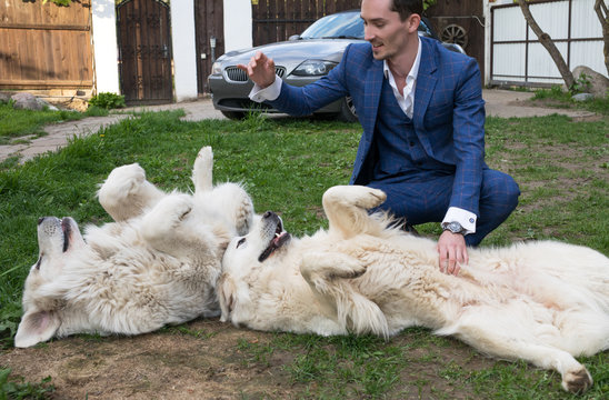 Elegant young handsome man in blue costume play with Tatra Shepherd Dog outdoor.