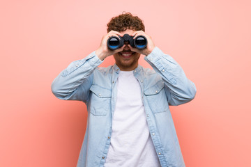 Blonde man over pink wall and looking in the distance with binoculars - fototapety na wymiar