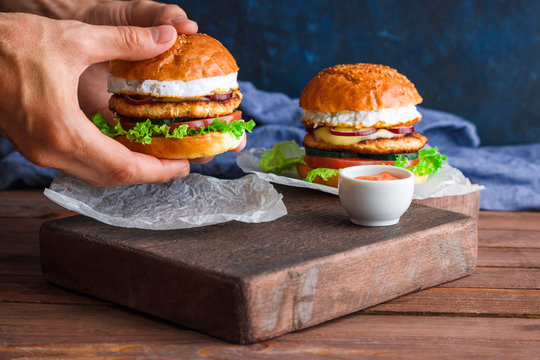 man hands holding chicken burger with fried egg cutlet lettuce red onion tomato