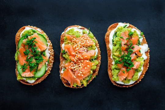 healthy sandwiches with rye bread salmon cream cheese avocado cucumber dill  on black background  top view
