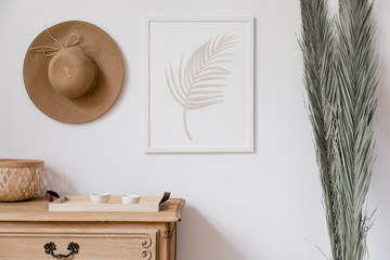 Stylish korean interior of living room with white mock up poster frame, elegant rattan accessories, wooden shelf, hanging hat and tropical palm leafs. Minimalistic concept of home decor. Template.  Wall mural
