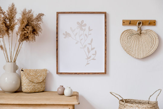 Stylish korean interior of living room with brown mock up poster frame, elegant accessories, flowers in vase, wooden shelf and hanging rattan leaf. Minimalistic concept of home decor. Template.