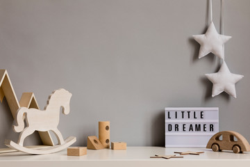 Stylish and cozy childroom with wooden mountain box, toys, rocking horse, blocks and hanging white stars on the gray wall. Bright and sunny interior. Copy space for inscription or product. Template.