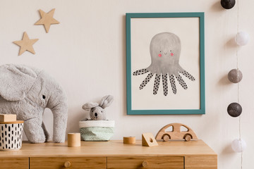 Stylish scandi childroom with blue mock up photo frame, wooden toys, boxes, plush elephant and rabbit. Stars pattern on the background wall. Bright and sunny interior with wooden desk. Home decor.