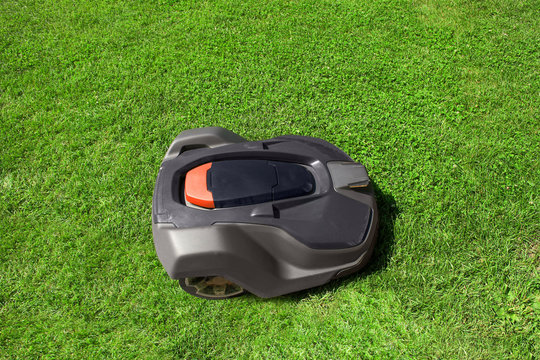 Automatic robot lawnmower mows grass on lawn, top view