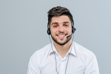 Handsome middle eastern man working with headset answering business calls as tech support dispatcher isolated over grey background