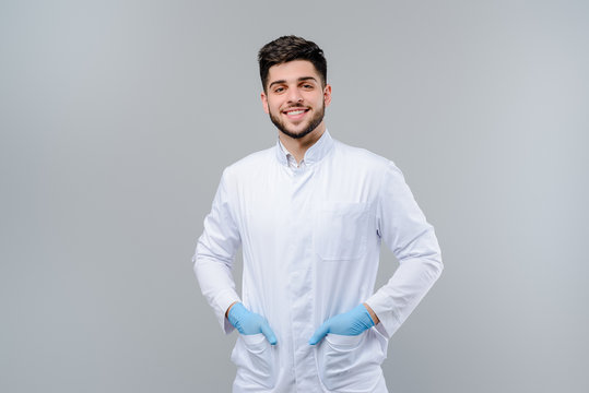 Handsome young medical doctor in gloves isolated over grey background