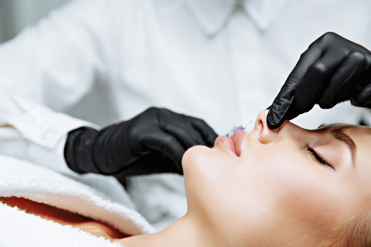 The doctor cosmetologist makes prick in the nose to correct the hump of a beautiful woman in a beauty salon.
