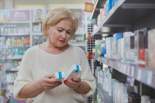 Senior woman choosing between two cosmetic products, shopping at the drugstore. Elderly female customer shopping for cosmetic or medical goods at pharmacy, copy space