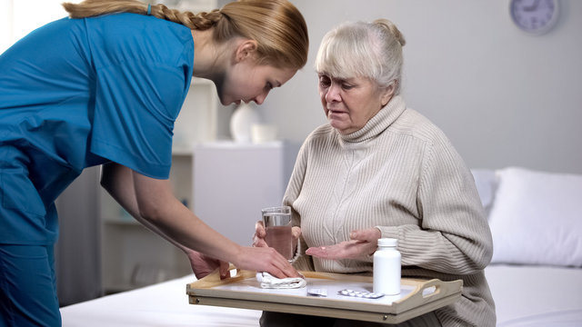 Elderly female patient spilling water on tray while taking pills, bad service