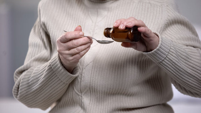 Old lady pouring cough syrup in spoon with trembling hands, health treatment