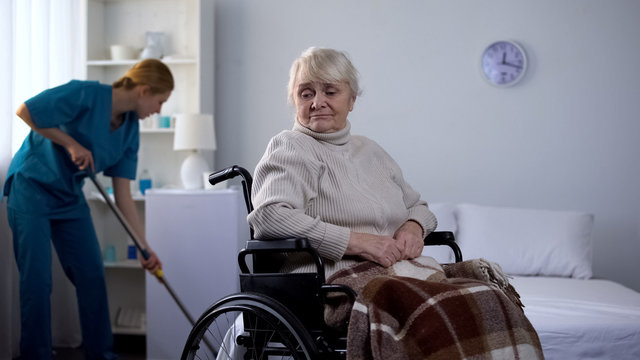 Sad woman in wheelchair watching hospital janitor cleaning room, medical center