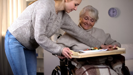 Female volunteer serving dinner to handicapped old woman, elder care, help