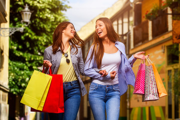 Shopping Mania! Two young women are happy after shopping. Smiling and walking down the street