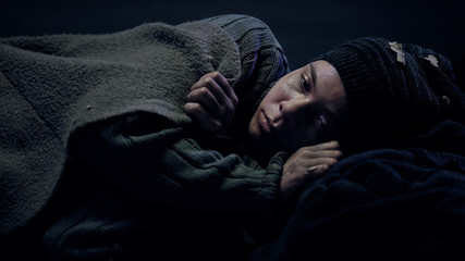 Crying refugee covered by blanket missing home and looking for shelter, poverty
