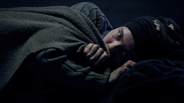 Freezing crying homeless woman looking at camera, taking cover, social problems