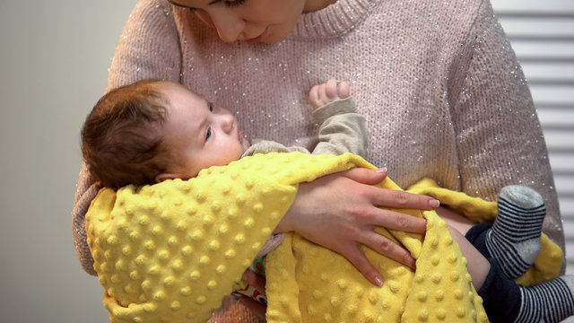 Beautiful young lady singing little baby to sleep, holding carefully in arms