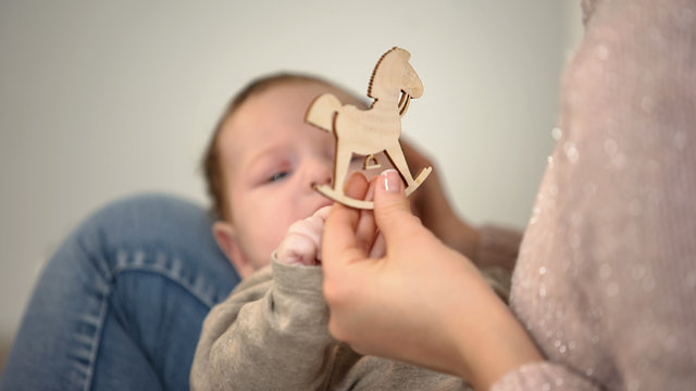 Female showing wooden horse figure to infant baby, early child development