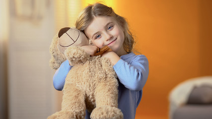 Beautiful girl with favourite teddy bear toy smiling at camera, happy childhood Wall mural