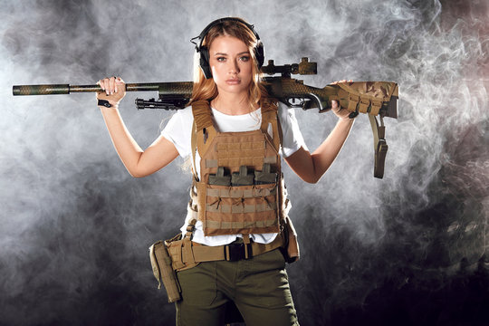 Woman soldier in military camouflage uniform protected with helmet, body armour, holding assault rifle standing against dark smoky background