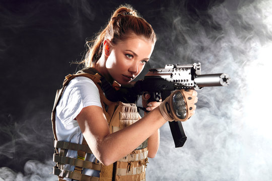 Calm concentrated woman marksman in sniper gear holding rifle in hand aiming at enemy s head in dark smoky background