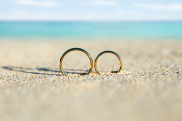 Golden And Shiny Wedding Rings On Beach
